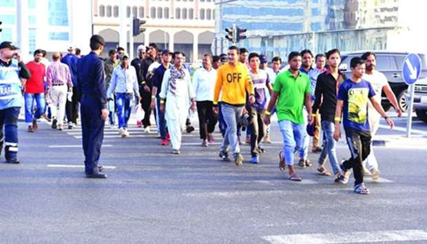 Officials guiding pedestrians to safely cross the road during an awareness building campaign.