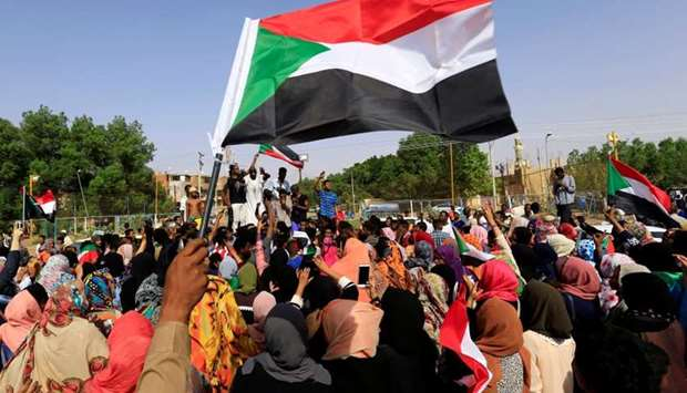 Sudanese people chant slogans and wave their national flag as they celebrate, after Sudan's ruling m
