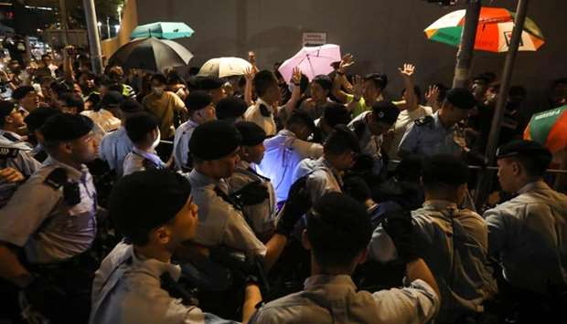 Policemen face protesters during a demonstration in the north-western district of Tuen Mun, near the