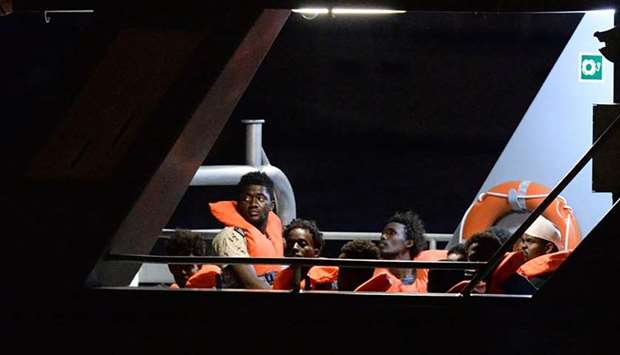 Migrants, part of group of 65 rescued by the German-flagged NGO rescue ship Alan Kurdi, look out fro