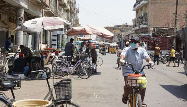A man wearing a face mask rides a bicycle along the Al-Sadriya Market in the Iraqi capital Baghdad a