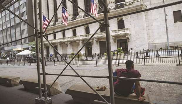 A person sits on a bench outside the New York Stock Exchange. Vanguard Group, the New York Stock Exc