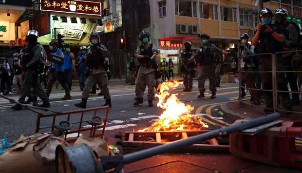 Riot police walk past a fire set by anti-national security law protesters during a march at the anni