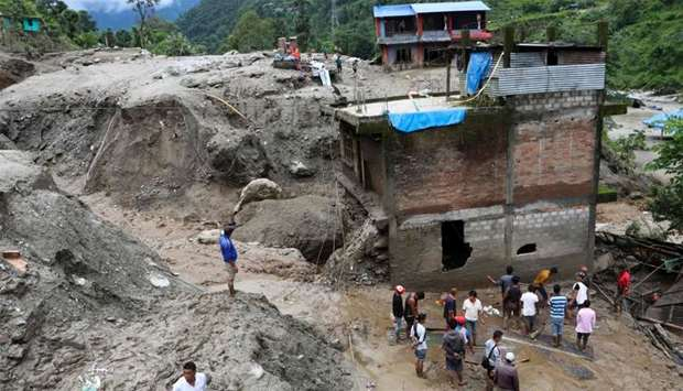 Residents and rescue workers inspect the area outside a house damaged by a landslide and the swell o