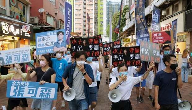Sam Cheung Ho-sum and Wong Ji-yuet march on a street to campaign for the primary election aimed at s
