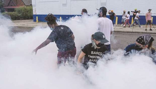 Protesters attempt to put out a tear-gas canister fired by Detroit police to disperse demonstrators
