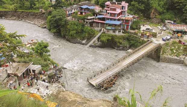 People gather near the bridge that is damaged due to the flood at Raghu Ganga River in Myagdi, yeste