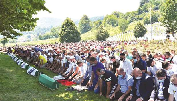 Bosnian Muslims wearing face masks pray during a burial ceremony yesterday at the Potocari memorial