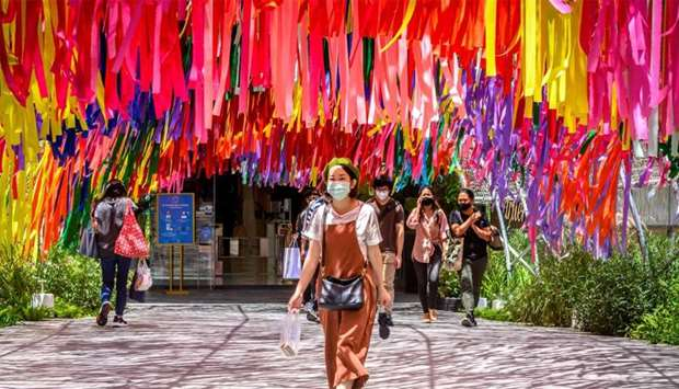A woman wearing a face mask walks out of a shopping mall in Bangkok
