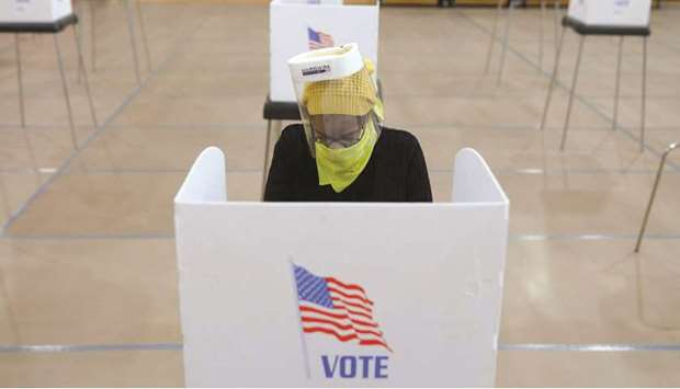 FILE PHOTO: Jocelyn Bush, a poll worker at the Edmondson Westside High School Polling site, cleans e