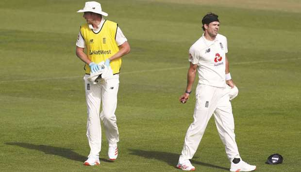 England's Stuart Broad (L) acts as twelfth man and assists England's James Anderson on the third day