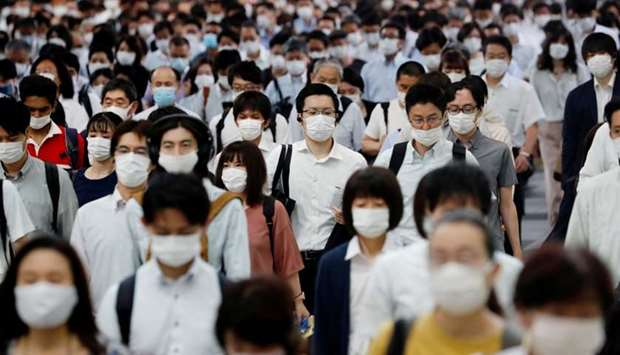 People wearing protective masks amid the coronavirus disease (COVID-19) outbreak, make their way dur