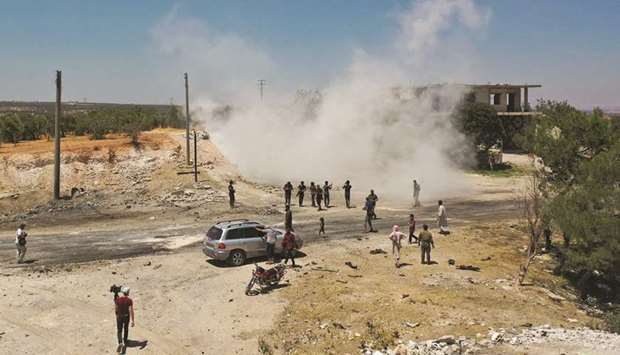An aerial picture shows Syrians gathering at the site of an improvised explosive device which hit a