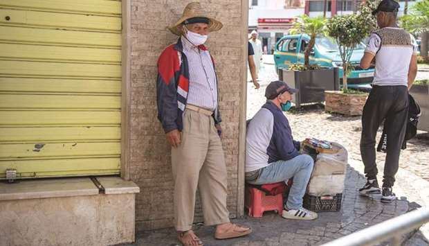 A Moroccan man, wearing a protective face mask, stands on a street corner in Tangiers' Old City.