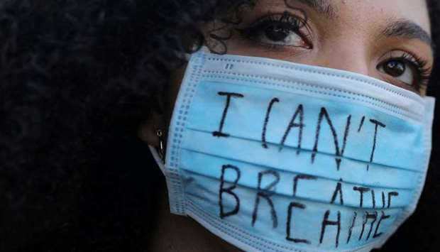 """RESONANT CRY: A woman wearing a face mask with the words """"I can't breathe"""" looks on during a protest"""