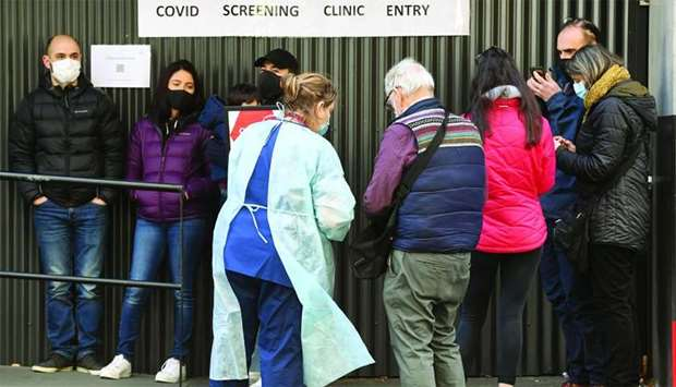 A medical worker speaks to people queueing outside a coronavirus testing venue at The Royal Melbourn