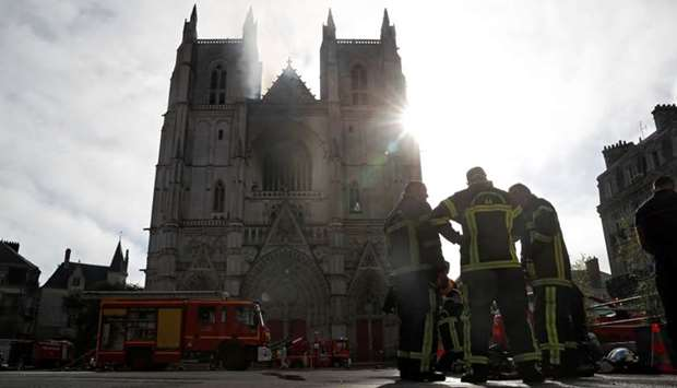 French firefighters gather at the scene of a blaze at the Cathedral of Saint Pierre and Saint Paul i