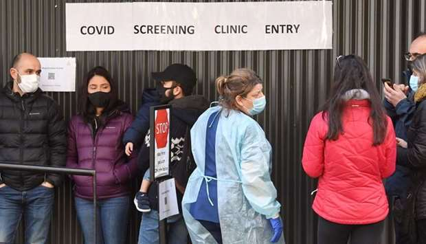 A medical worker (C) speaks to people queueing outside a Covid-19 coronavirus testing venue at The R