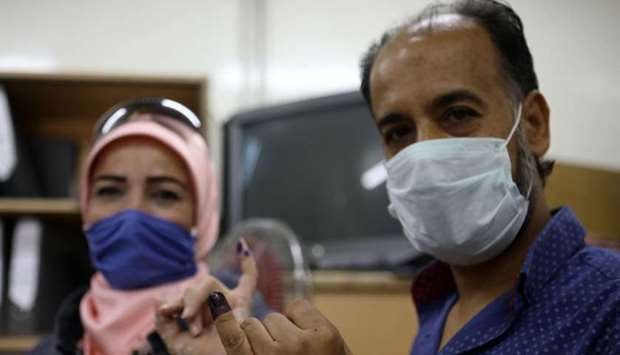 A man and a woman show their ink-stained fingers after voting at a polling station in the Syrian cap