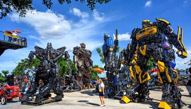 "Tourists taking photos of life-sized sculptures of characters from the ""Transformers"" film franchise"