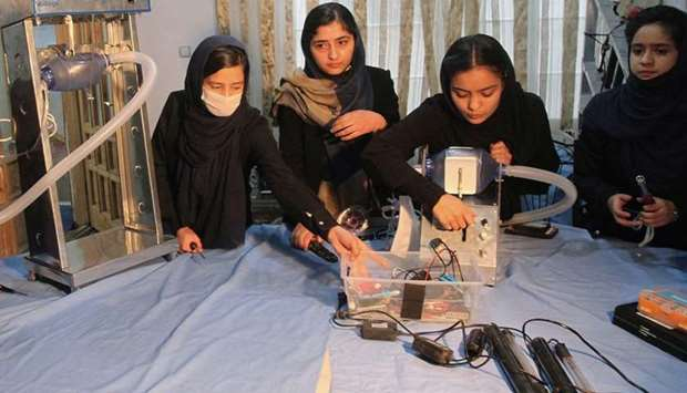 Members of an Afghan all-female robotics team work on an open-source and low-cost ventilator, during