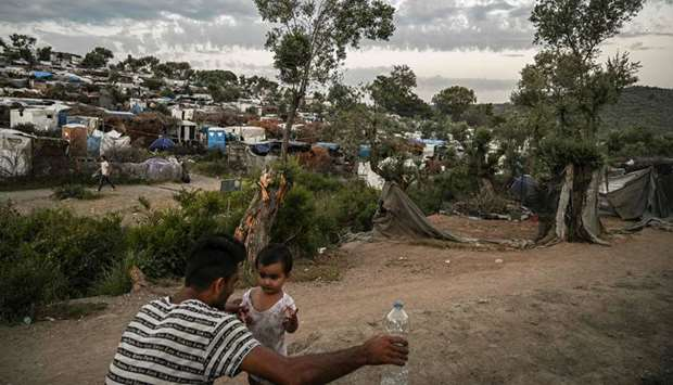 A man with a child is pictured in a improvised tents camp near the refugee camp of Moria in the isla