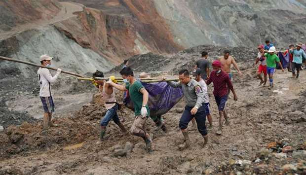 Rescuers recover bodies near the landslide area in the jade mining site in Hpakhant in Kachin state