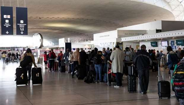 Travellers queue at the Ailitalia and Air France-KLM flight check in desks as European Union travel
