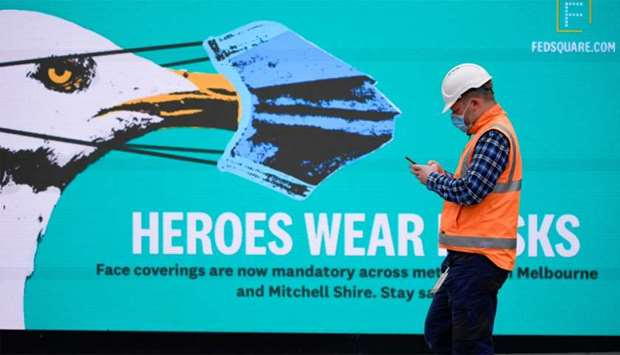 An essential worker wearing a face mask walks past a 'Heroes Wear Masks' sign in Melbourne