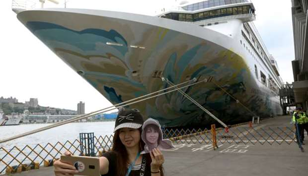 A woman takes a selfie in front of the Explorer Dream cruise ship, in Keelung, Taiwan