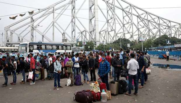 Migrant workers wait in lines for transport outside the Howrah railway station after authorities ann