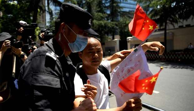 """A man holds a banner and shouts """"Chinese government is great"""" is escourted by policemen in front of"""