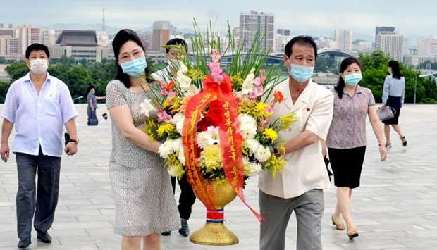 People wearing face masks pay a floral tribute to statues of North Korea's founder Kim Il Sung and l