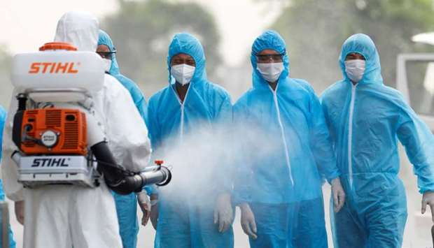 A health worker in a white protective suit sprays disinfectant at Vietnamese construction workers in