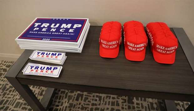 Trump re-election campaign signs and 'Make America Great Again' hats sit on a table outside a campai