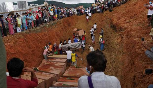 Volunteers bury bodies of miners in a mass grave while relatives look on during a funeral ceremony n