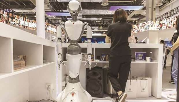 An attendant stands next to a CloudMinds Technology XR-1 commercial humanoid service robot at the Wo