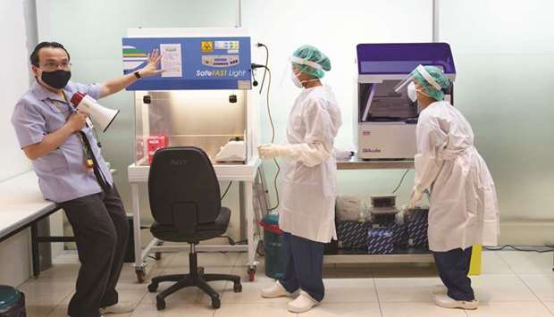 A doctor and medical staff wearing personnel protective equipment (PPE) demonstrate the lab workflow
