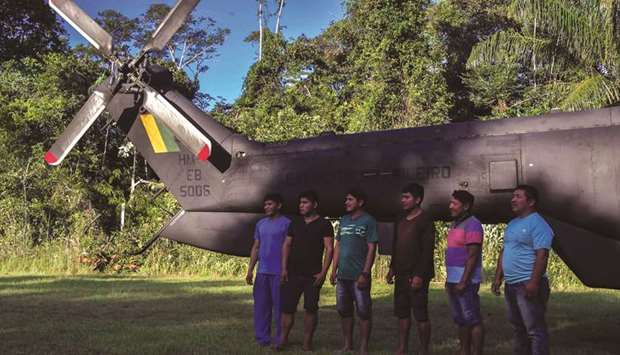 Indigenous Ye'kuana pose in front of a helicopter at the 5th Special Frontier Platoon in Auari, Rora