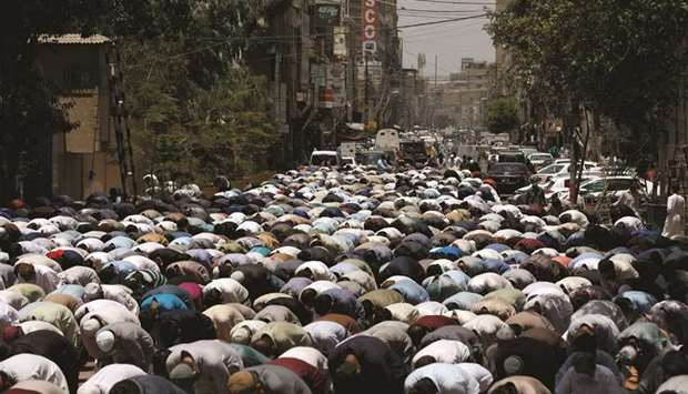 People attend Friday prayers yesterday along a road in Karachi, after the authorities re-imposed loc