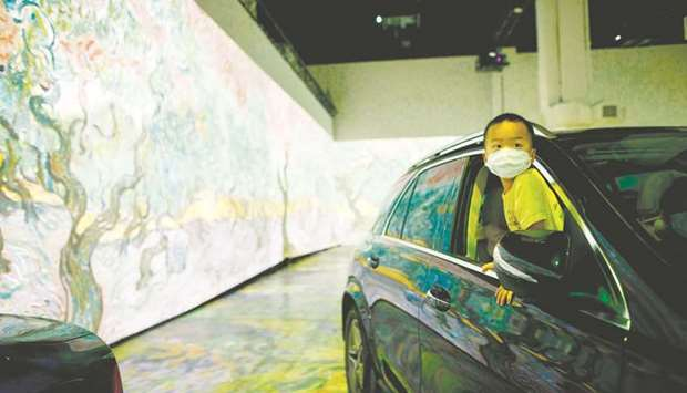 Tyler Tsang, 4, peeks out of the car as he experiences a drive-in immersive Vincent Van Gogh art exh