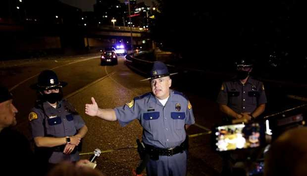 Washington State Patrol Capt. Ron Mead briefs media near the scene where two people in a group of pr
