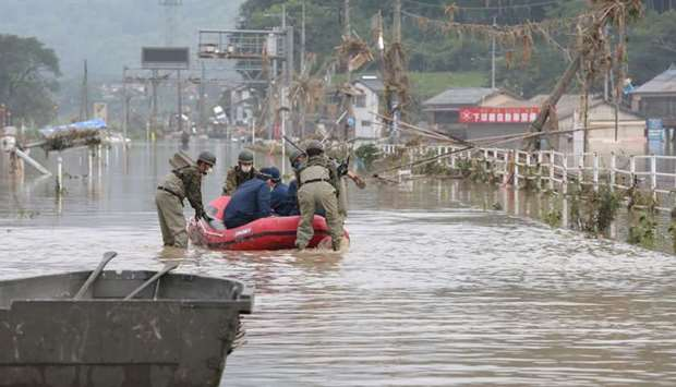 Japan Self-Defense Forces and police officers handle an inflatable boat to join rescue operations at