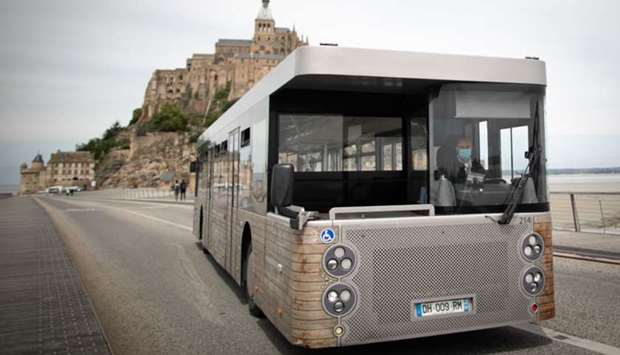 "A driver wearing a protective mask sits in a shuttle bus in front of ""Le Mont-Saint-Michel"", in Norm"