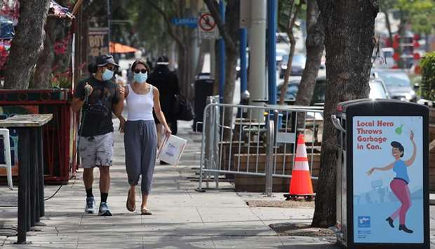 GETTING IN ON THE ACT: A couple walk along Santa Monica Boulevard last Thursday in West Hollywood, C