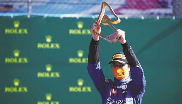 McLaren's Lando Norris celebrates with the trophy on the podium after finishing third at the Austria
