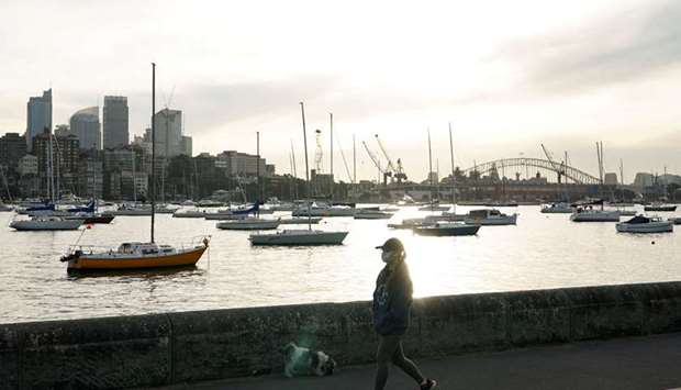 A woman wearing a protective face mask walks along a waterfront path during a lockdown to curb the s