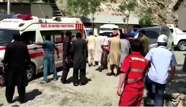 People wheel a gurney towards an ambulance outside a hospital in Dasu, after a bus with Chinese nati