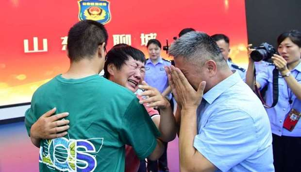 Guo Gangtang, 51, and his wife reunite with their son Guo Xinzhen, who was abducted 24 years ago at