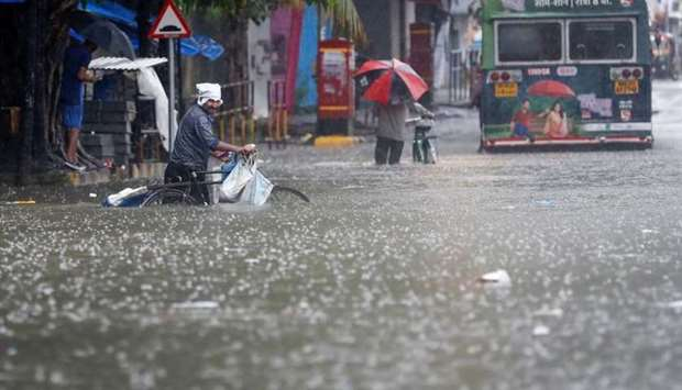 People wade through a waterlogged road after heavy rainfall in Mumbai, India, July 16